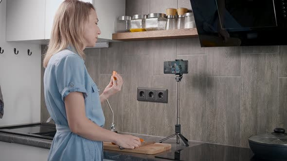 A Housewife in Her Kitchen Prepares Food and Communicates Online