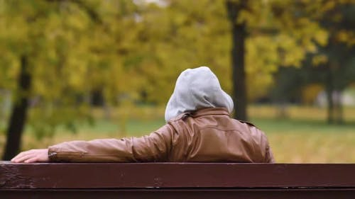 Unknown man in a hood sitting on a park bench is watching
