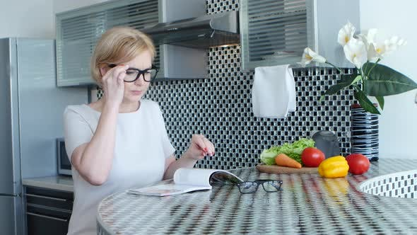 Thumbnail for Woman Is Sitting in the Kitchen at the Table and Reading a Recipe for a Dish
