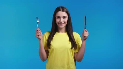 Porträt einer hungrigen Frau mit Gabel und Messer