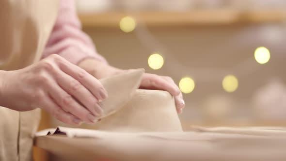 Thumbnail for Hands of Anonymous Femelle Potter Grattage Bol en argile humide avec outil
