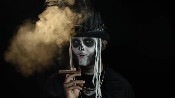 Sinister Man with Horrible Halloween Skeleton Makeup Smoking Cigar, Making Faces, Looking at Camera