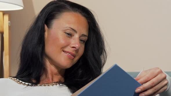 Thumbnail for Attractive Mature Woman Smiling Joyfully Reading Interesting Book