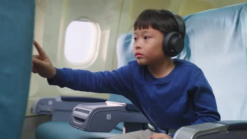Asian young little boy touching at video screen then watching movie and cartoon sitting on airplane.