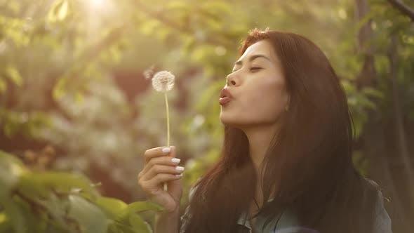 Woman Blow on Dandelion at Garden