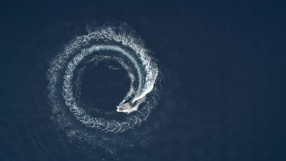 Thumbnail for Aerial view of a boat driving in circles forming waves around in Greece.