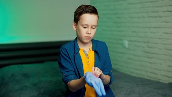 Thumbnail for Boy puts on rubber gloves