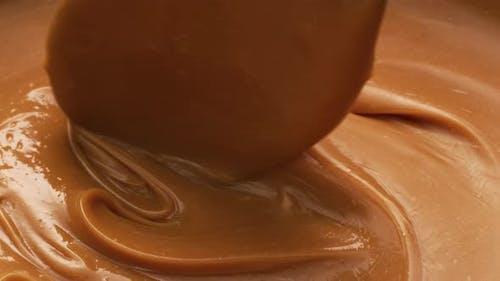 Stirring melted caramel, closeup food shot.