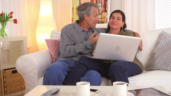 Happy senior couple making vacation reservations on laptop