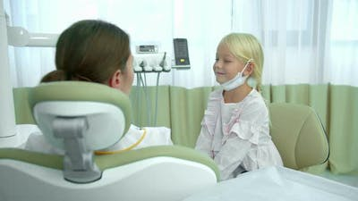 Girl Sit in Dentists Chair and Talks with Dentist