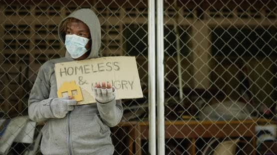 Homeless holding homeless and hungry label.