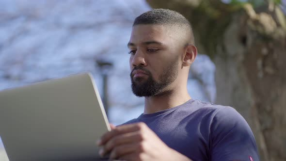 Thumbnail for Bottom View of Young Man in Park Opening Laptop, Thinking