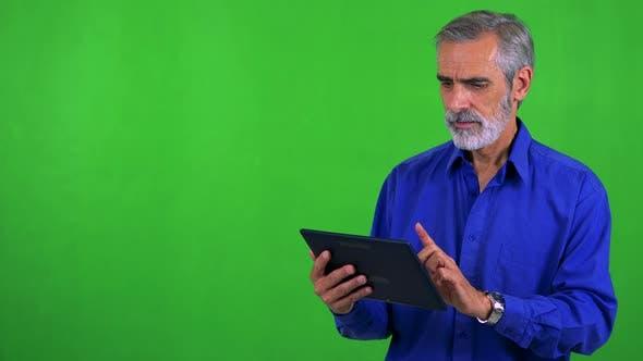 Thumbnail for Old Senior Man Works on Tablet - Green Screen - Studio