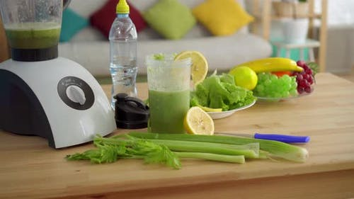 Concept Idea of Proper Nutrition, on the Table Celery Smoothies, Lemons, Salad,fruit and Water