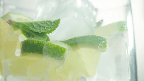 Pouring Sparkling Water Into Glass with Ice Lime and Mint