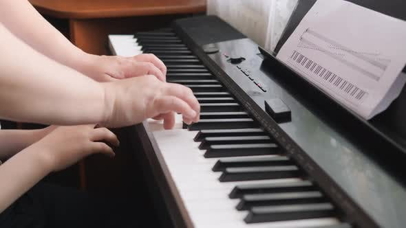 Thumbnail for Children's Hands on a Keyboard Instrument. The Hands of an Adult Press the White Keys. The Child