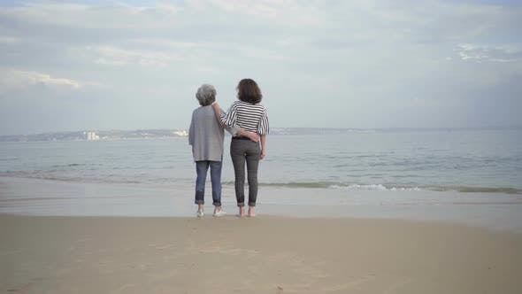 Thumbnail for Two Smiling Women Hugging on Sandy Beach and Pointing at Distance