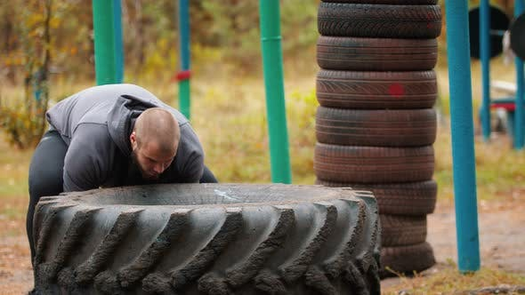 Thumbnail for A Big Man Bodybuilder Turning Over the Tire on the Ground - Training Outdoors