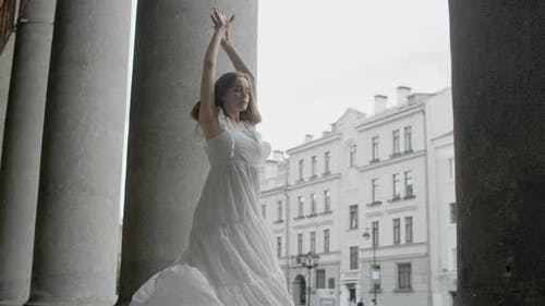 Young Balerine in White Dress Whirls on the Stairs of the Theatre in Slow Motion Balerine Dances