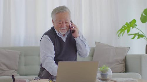 Asian senior handsome business man hold mobile phone talking with business team and meeting online
