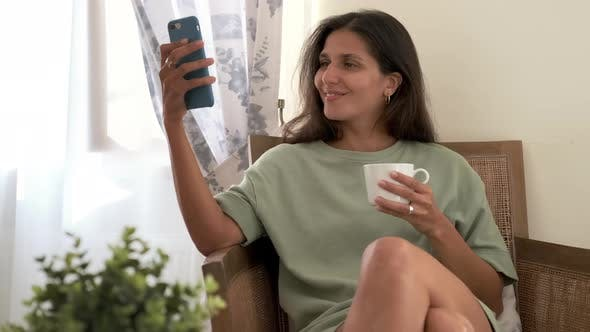 Happy Woman is Viewing Pictures in Social Nets Using Smartphone Relaxing Alone at Home