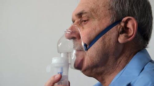 Senior Man Inhaling Through Inhaler Mask