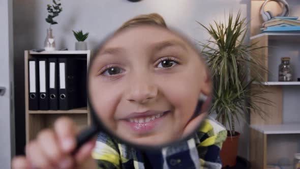 Thumbnail for Good-Looking Smiling Teen Boy Looking Through the Magnifying Glass at Home