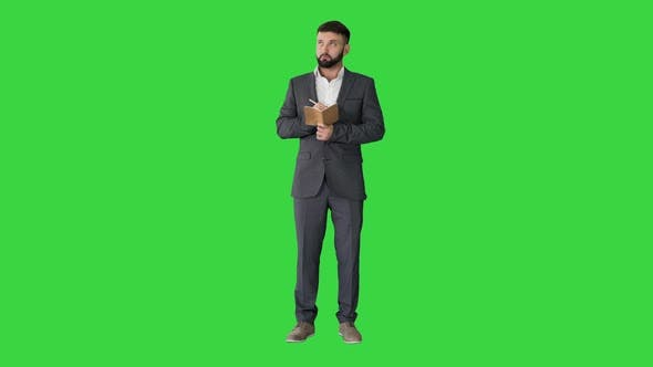 Thumbnail for Concentrated Young Man in Formalwear Holding Note Pad and Writing on a Green Screen, Chroma Key