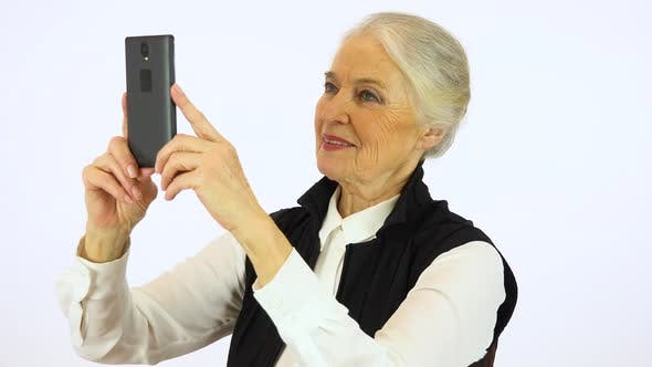 Thumbnail for An elderly woman takes selfies with a smartphone - white screen studio