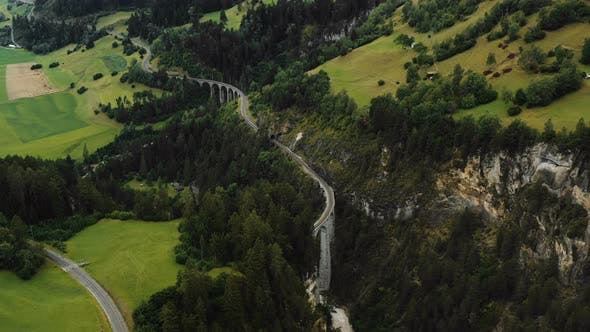 Amazing Panoramic Aerial Shot of Famous Swiss Alps Railway Passes, Epic Zoom in on Famous Landwasser