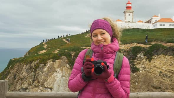 Thumbnail for Girl with Camera Poses Against Lighthouse on Hilly Coast