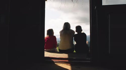 Mother with Kids Sitting on Porch Together