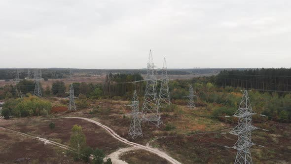 Transmission electricity steel pylon towers in forest. Electric tower lines. Environmental problem