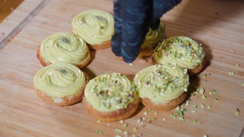 Small Pieces of Pistachio are Placed on Pastries with Custard