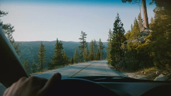 Thumbnail for Beautiful First Person View of Male Hand Holding Car Steering Wheel Driving Along Mountain Road