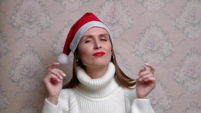 Young Positive Dancing Woman with Christmas Cap and Headphones
