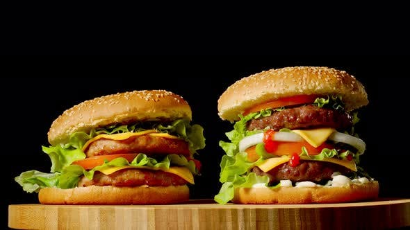 Thumbnail for Two Craft Beef Burgers on Wooden Table Isolated on Dark Grayscale Background