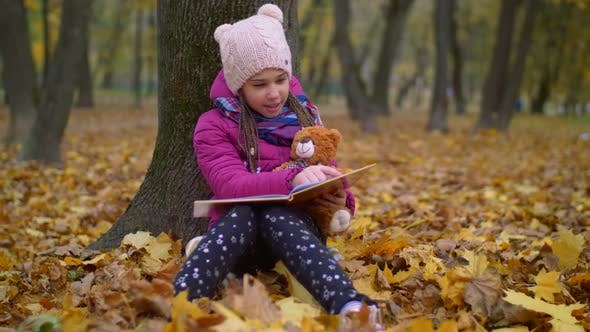 Thumbnail for Cute Girl Reading Book Under the Tree in Autumn Park