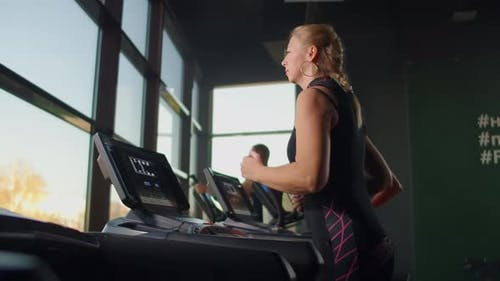 A Group of People Running on Treadmills Near a Large Panoramic Window. Group Cardio Workout.