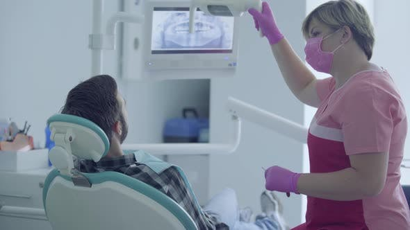 Thumbnail for Dentist in Medical Mask and Gloves Checking the Mouth of the Patient Using Medical Tools