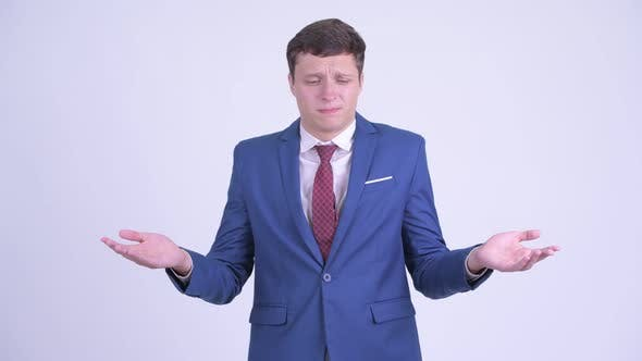 Cover Image for Confused Young Businessman Shrugging Shoulders