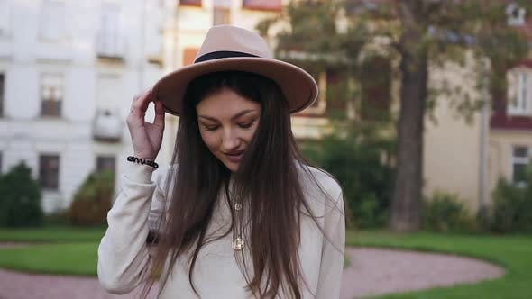 Thumbnail for Girl with Trendy Hat Walking on the Beautiful Mansions Background and Looking at Camera