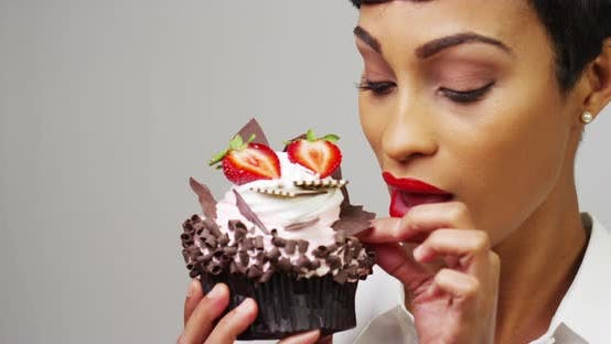 Thumbnail for Woman admiring a fancy dessert cupcake with chocolate and strawberries