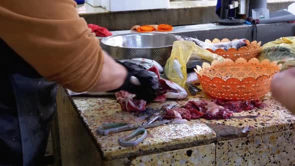 Cutting Fish in Market Stall. Woman Manual Cleaning and Cuts Fresh Fish