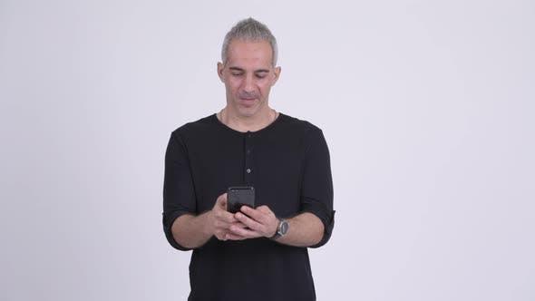 Happy Handsome Persian Man Using Phone