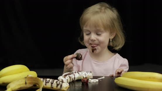 Thumbnail for Child Eats Banana, Strawberry with Melted Chocolate and Whipped Cream