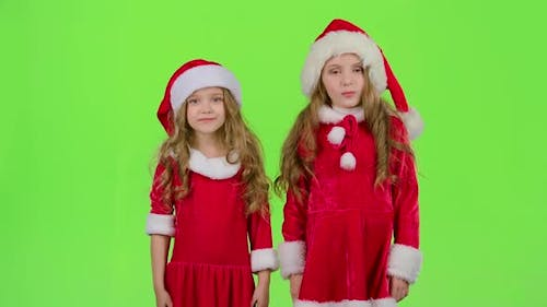 Children in a Red Suit Are Standing in the Room and Wink. Green Screen