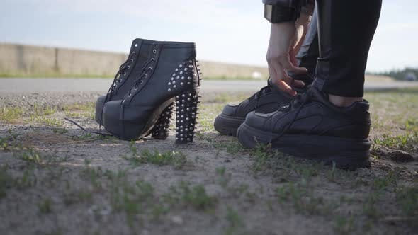 Thumbnail for The Young Woman Changing Her Motorcycle Shoes on Spiked Shoes with High Heels