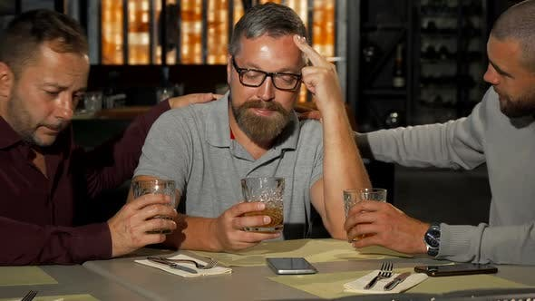 Thumbnail for Two Mature Men Supporting Their Upset Friend While Drinking at the Bar