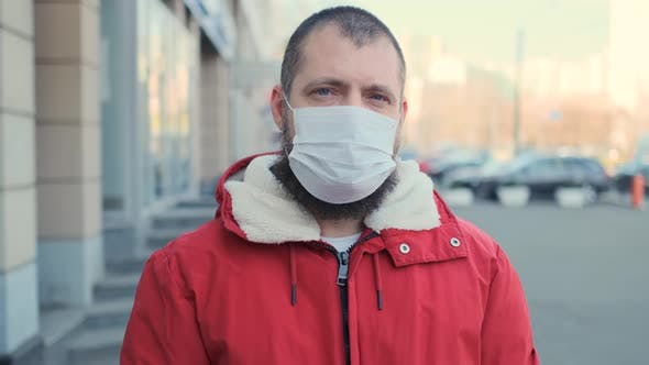 Thumbnail for Bearded Man Wearing Protective Face Mask and Look at Camera Serious Pandemic Disease Virus. COVID-19